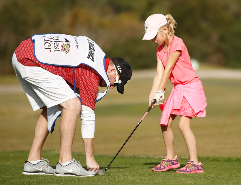 girl getting a golf lesson