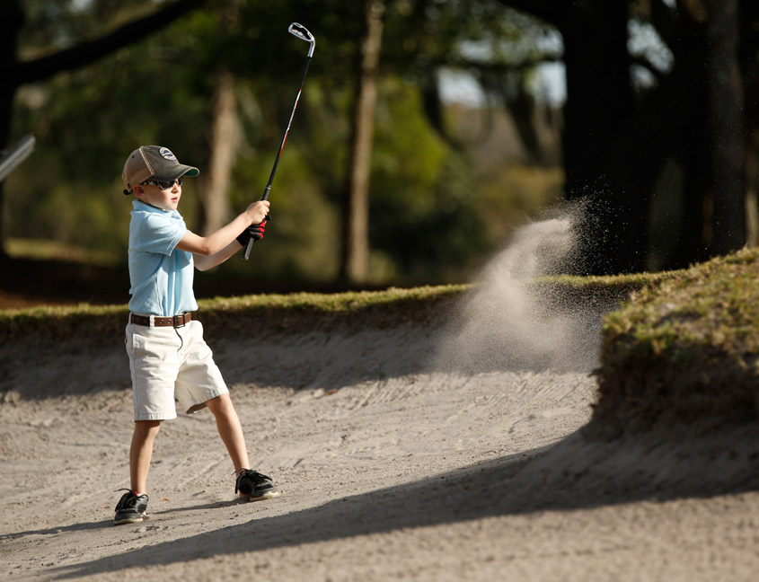 boy hitting golf ball out of sand