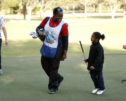 little girl golfing with mom