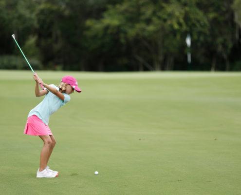 girl hitting golf ball to green