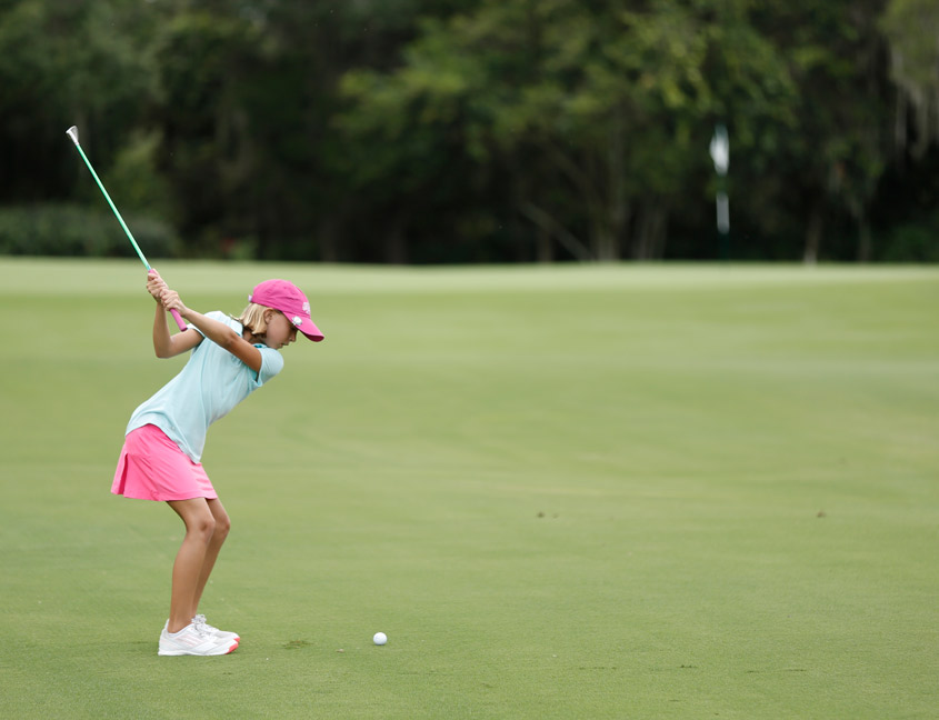 girl hitting golf ball to green