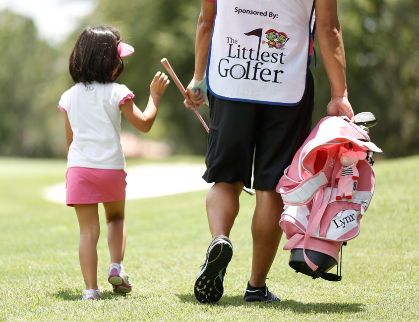 little girl golfing with parent