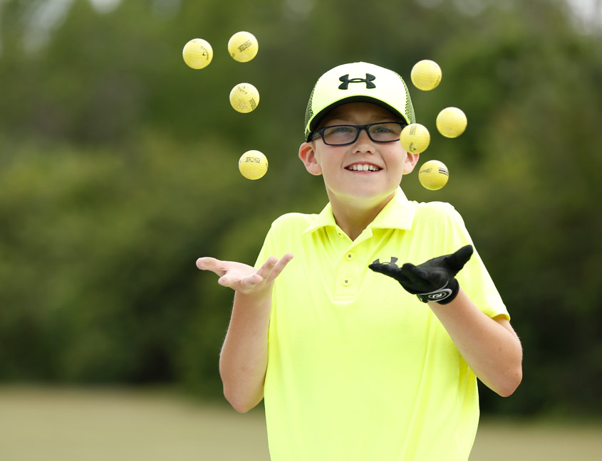 boy tossing golf balls