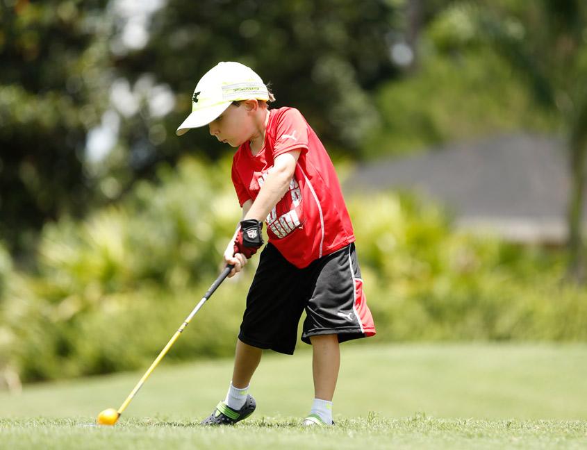 little kid hitting a golf ball