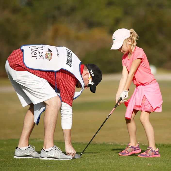 coach-helping-girl-on-driving-range