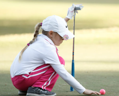 girl-marking-golf-ball-on-green