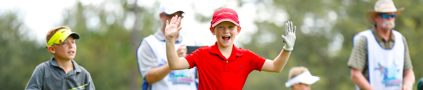 kid playing golf in red shirt